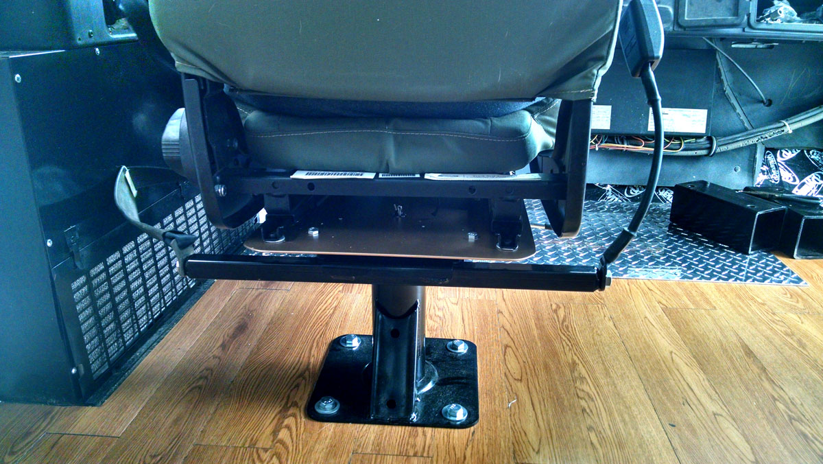 Custom made Skoolie driver's seat adapter plate in action.