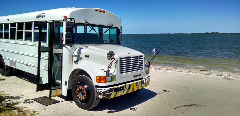 Our Skoolie parked on the beach at Sanibel Island causeway